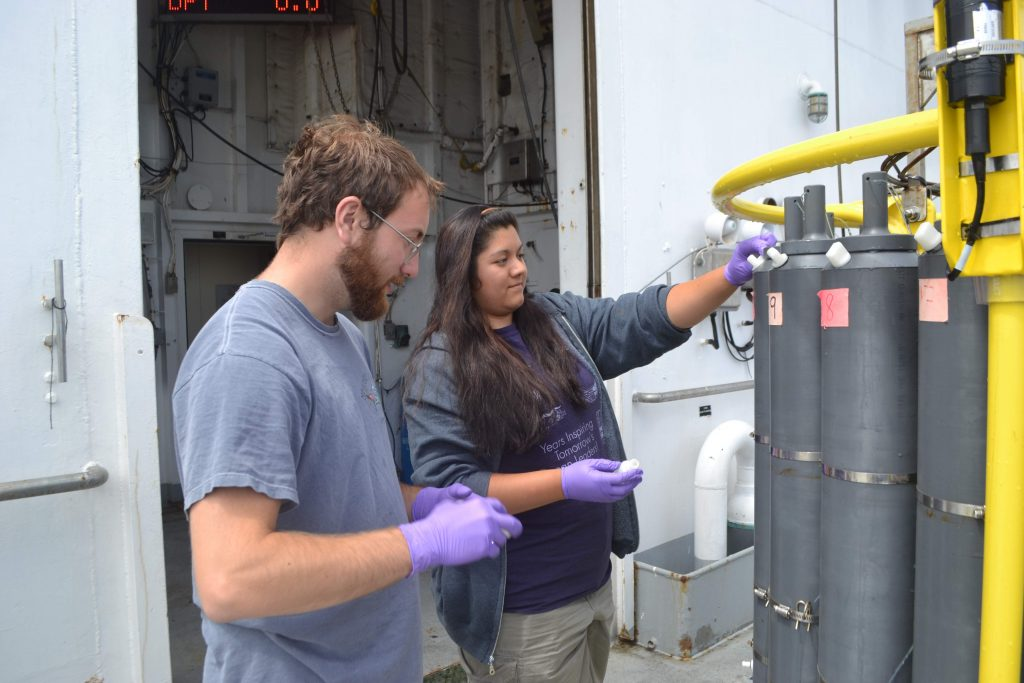 Katie Gonzalez and Willem Weertman take water samples from the first CTD cast on the VISIONS17, OOI-NSF cruise. Credit: M. Elend, University of Washington.