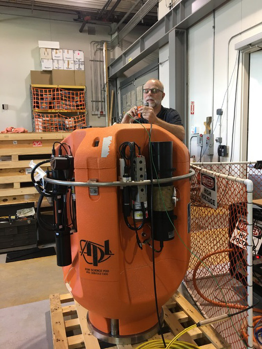 Eric McRae, an engineer at the UW Applied Physics Laboratory, checks out an instrumented science pod to be installed on a Shallow Profiler Mooring during the VISIONS'17 cruise. Credit: D. Kelley, University of Washington.