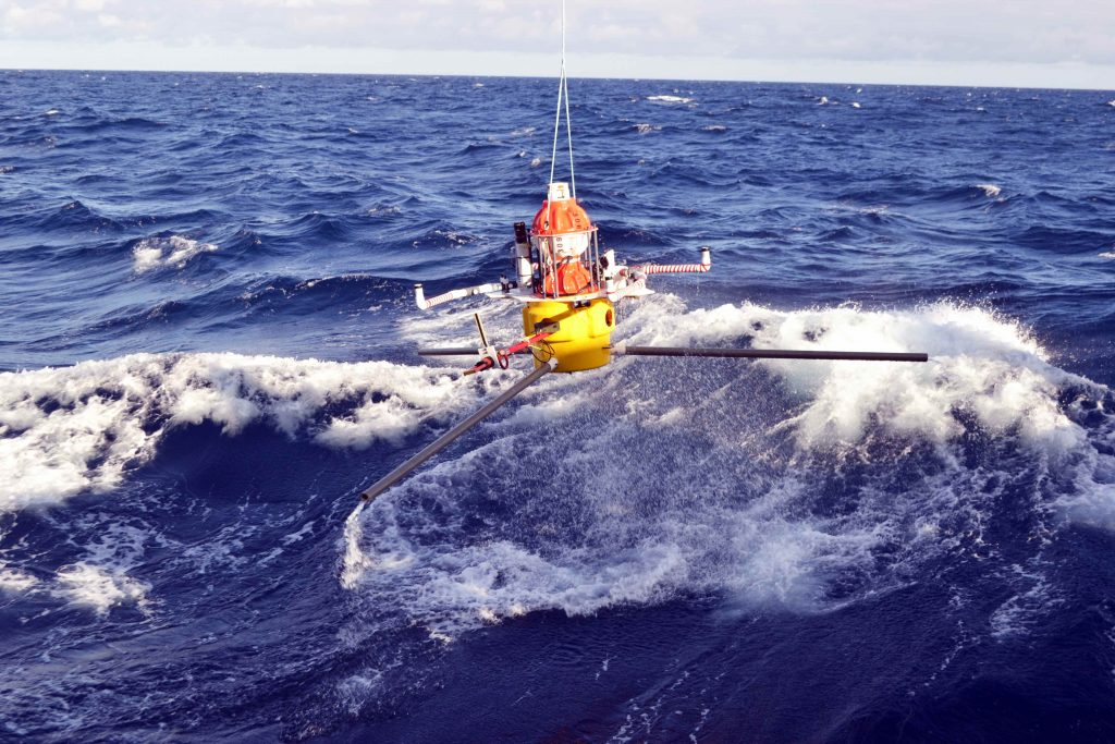 An HPIES instrument deployed off the starboard side of the R/V Sikuliaq ~ 125 km offshore Newport Oregon near the base of the Subduction Zone. The instrument was released and free fell over 9000 ft to land softly on the seafloor - the extended legs insure a softer landing and that is stays nearly horizonatal as it travels throught the water column. This instrument utilizes a bottom pressure sensor, an inverted echosounder and a horizontal electrometer to provide insights into the vertical structure of current fields, near-bottom water currents, and water properties including temperature, salinity, and specific volume anomalies. It was built at the Applied Physics Laboratory. Credit: M. Elend, University of Washington, V16.