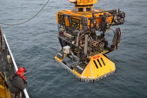 A trawl-resistant Benthic Experiment Package is latched under ROPOS and ready for deployment at the EA Shelf (60 m) Site. Credit: Mitch Elend, UW; V15.