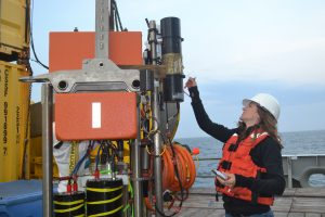 Trina (APL-UW) does final preparation and checkout of a SAMI-pH sensor before the Platform Interface Controller is deployed. Credit: Mitch Elend (UW);V15.