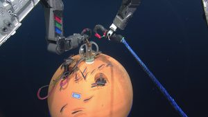 During Dive R1862, ROPOS attaches a line to the float on the deep profiler mooring at Axial Base in preparation for its recovery. Credit: NSF-OOI/UW/ISS; V15.