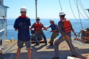 Eric Boget from the Applied Physics Lab and Brian Clampitt from the R/V Thompson work to bring teh anchor for the Deep Profiler Mooring onboard during Leg 2 of the VISIONS'15 cruise. Credit: University of Washington, V15.