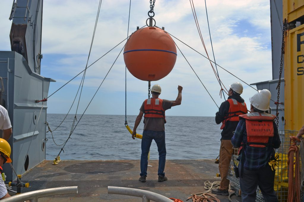 The Deep Profiler Float from the Slope Base site being installed off the fantail of the R/V Thompson during Leg 2 of the OOI-NSF- Cabled Array VISIONS'15 cruise. Eric Boget from the UW Applied Physcis lab leads the deck operations. Credit: Mitch Elend, University of Washington; V15.