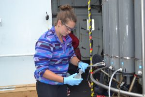 University of Washington undergraduate, Jessie Hild, takes water samples for follow-on analyses from Niskin bottles onboard the R/V Thompson during the Cabled Array VISIONS'15 expedition. Credit: Mitch Elend, University of Washington.