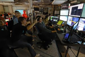 Katie Bigham, a junior in the School of Oceanography, takes her first turn at directing ROPOS operations inside the control room. She is studying the distribution of methane seeps and biological communities at Southern Hydrate Ridge. Credti: Ed McNichol, V15.