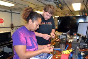 Ben Brand shows Kearstin the 'ropes' in making multicolored monkey fists. Credit: Mitch Elend, University of Washington, V15.
