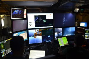 The ROPOS control room onboard the R/V Thompson as it works at the 18 m tall (59 ft) actively venting chimney called El Guapo in the International District Hydrothermal Field. Credit: Mitch Elend, University of Washington, V15.