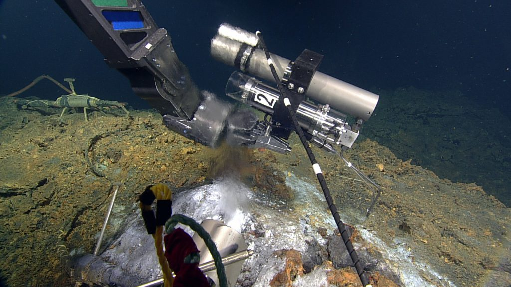 The RO ROPOS holds a 'IGT' gas tight bottle in the orifice of the 280°C chimney called Diva. The high temperature fluids exiting the seafloor at this anhydrite-rich (CaSO4) vent contain the highest carbon dioxide concentrations at Axial Seamount. Credit: NSF-OOI/UW/ISS; Dive R1836; V15.
