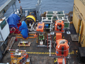 The fantail of the R/V Thompson loaded with junction boxes, science pods for the Shallow Profiler Moorings, and a variety of instruments. Credit: Jesse Turner, University of Washington, V15.