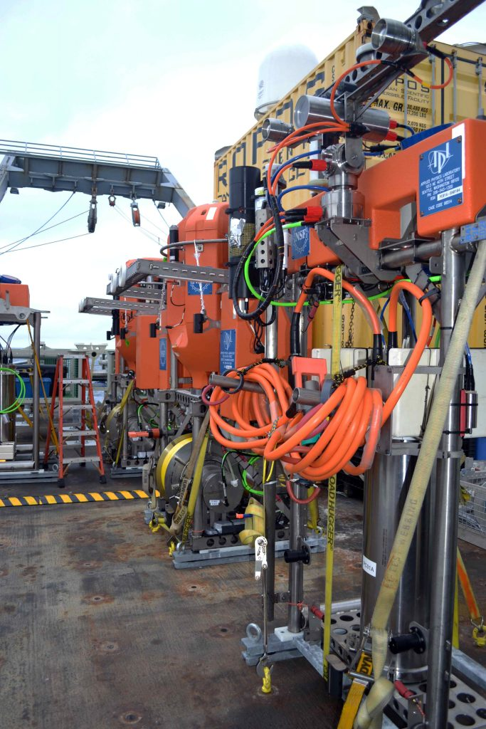 A line of shallow winched profilers and instrumented platform interface assemblies await installation on  2-legged Shallow Profiler Moorings that provide real-time data on chemical, biological, and physical properties of ocean waters off the coast of Oregon. Credit. Deb Kelley, University of Washington, V15.