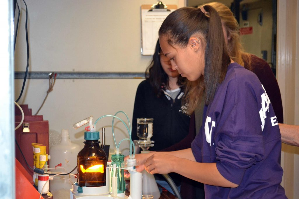 Kadijah learns how to do titration analyses of dissolved oxygen in fluids from up to 1000 m water depth on the VISIONS'15 cruise. Credit: Deb Kelley, University of Washington.