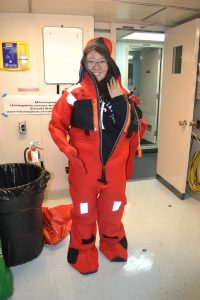 Diana successfully gets into a survivial suit during safety training on the first day of the Cabled Array VISIONS15 expedition. Credit: Mitch Elend, University of Washington, V15.