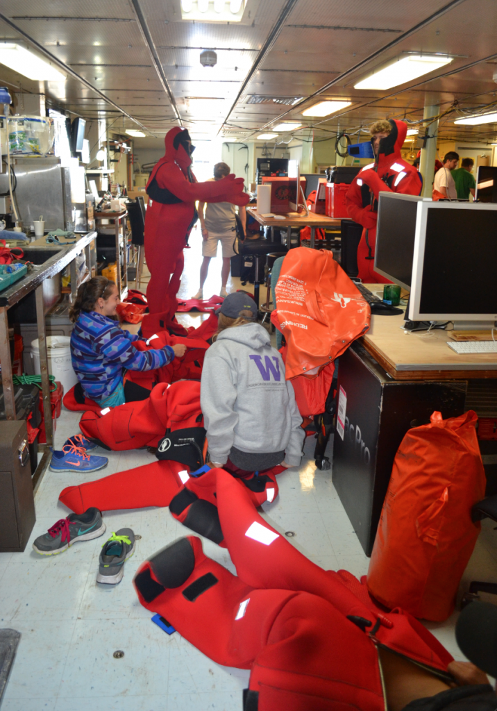 Undergraduate students from the UW School of Oceanography practice getting into emergency immersion suits during the first leg of the Cabled Array VISIONS'15 cruise. Credit: Mitch Elend, University of Washington.