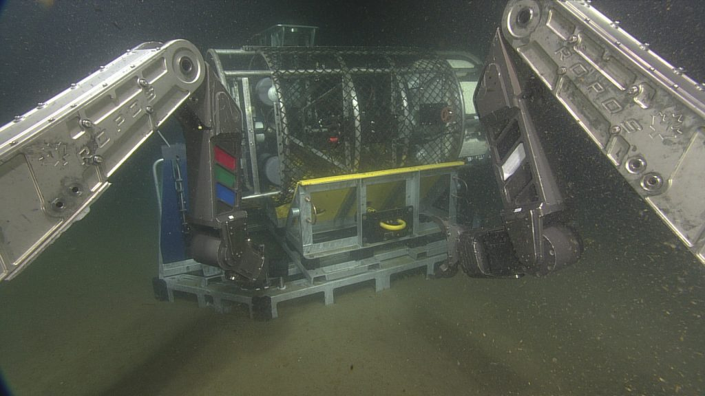 ROPOS using the starboard manipulator to pull the release that allowed the sensor pod of the cabled coastal surface-piercing profiler (cCSPP) to swing upwards and float freely in the water. The cCSPP was delivered to the seafloor and placed roughly 12 meters due East of the medium-powered junction box MJ01C at the Oregon Shelf site, in 79 meters of water.    Photo Credit: NSF/UW/CSSF, Dive R1801, V14