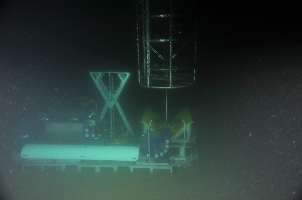 The sensor pod of the cabled coastal surface-piercing profiler (cCSPP) floating freely in the water column after being released from the deployment cradle on the profiler base. Once powered up, the sensor pod will move up and down in the water column at least 4 times per day, taking samples continuously using the onboard CTD, oxygen, fluorometer, nitrate, AC-S, PAR sensor, spectral irradiance, and 3D water velocity sensors.    Photo Credit: NSF/UW/CSSF, Dive R1801, V14