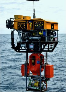 The instrumented science pod and winched profiler system are latched beneath the ROV ROPOS for safe transport to the Oregon Offshore mooring where it will be installed on the 13 ft across platform at 197 m water depth. Photo Credit. Billy Medwedeff, University of Washington, V14.