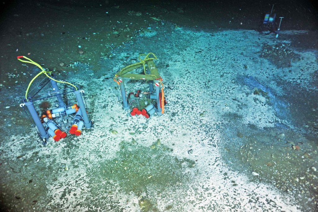 "A ""Mosquito"" flow meter (far left) and osmotic fluid sampler (far right) are installed in an active methane seep at Southern Hydrate Ridge. A second Mosquito, colonized by organisms, awaits recovery. These instruments provide fluid chemistry information, as well as calculations of fluid flow in and out of the seafloor. Photo credit: NSF-OOI/UW/CSSF; Dive R1772; V14."