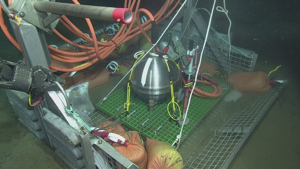The Slope Base seismometer and hydrophone in the ROPOS toolbasket, prior to deployment in the previously excavated caisson.  Photo Credit: NSF-OOI/UW/CSSF, Dive R1751, VISIONS14