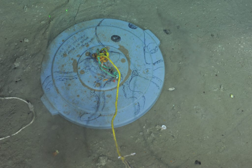 A caisson lid at Hydrate Ridge that was decorated with an octopus and a Basho haiku during a previous VISIONS cruise.  Photo Credit: NSF-OOI/UW/CSSF, Dive R1750, V14