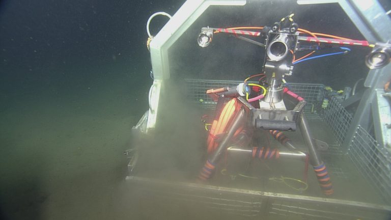 The digital stil camera in the ROPOS toolbasket during deployment at Endurance Oregon Offshore site (600 m).Unlike the cameras placed at Axial Volcano, the camera at Endurance Offshore is designed to look at the seafloor in general, observing animal activity, sediment transport, detritus falls, and bioturbation.  Photo Credit: NSF-OOI/UW/CSSF, Dive 1747, V14