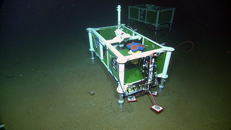 An Acousitic Doppler Current Profiler (four blue-red cyllinders with yellow housing) is installed at the base of Axial Seamount near PN3A on ROPOS Dive R1735. It is housed within the medium powered junction box MJ03A. Photo Credit: NSF-OOI/UW/CSSF; Dive R1735; V14