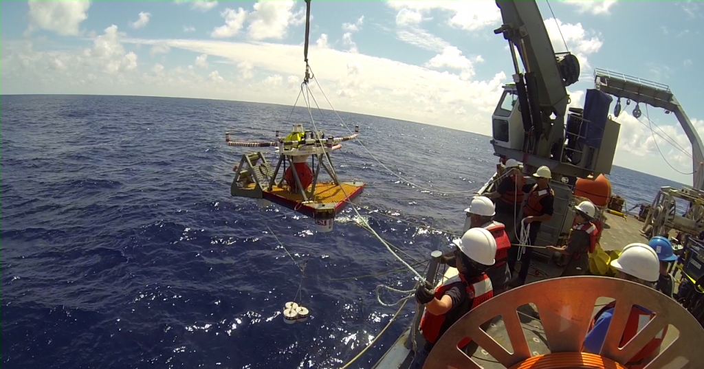 The HPIES instrument is being lowered over the side of the R/V Thompson for installation at the base of Axial Seamount. The HPIES (Horizontal Electrometer Pressure Inverted Echosounder) measures the horizontal electrical field, the bottom pressure, and the acoustic travel time from the seafloor to the sea surface to characterize the properties of the water column.
