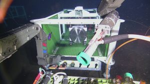 ROPOS removing the protective cap from the P1 end of cable AXVMW4, prior to plugging it into low-voltage node LV03A at Axial Base.  Photo Credit: NSF-OOI/UW/CSSF, Dive 1737, V14