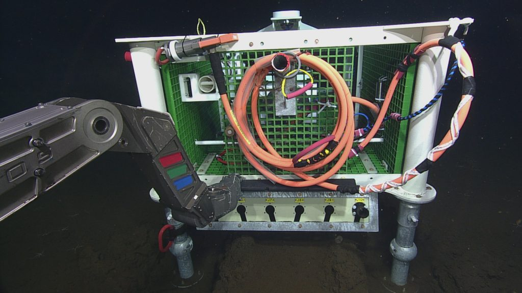 ROPOS about to plug junction box LJ03A into low-voltage node LV03A at the Axial Base site.  	Photo Credit: NSF-OOI/UW/CSSF; Dive 1736; V14.