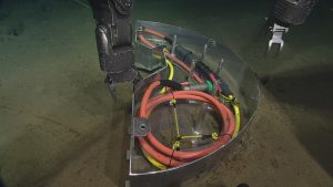 The port arm of ROPOS reaching for the connector in a flange box on the seafloor at the Slope Base site.  	Photo Credit: NSF-OOI/UW/CSSF; Dive 1734; V14.