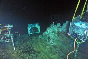 """During ROPOS Dive R1729, a digital-still camera (left), a mass spectrometer (middle) and a fluid- and microbial-DNA sampler (right) were installed in the International District Hydrothermal Field at the vent called El Gordo. A titanium """"hat"""" rests on top of the structure in a tubeworm and limpet patch. Inside the """"hat"""" are temperature probes and intake nozzles for the fluid and DNA sampler. Photo credit: NSF-OOI/UW/CSSF; Dive R1729; V14."""