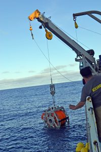 The ROCLS cable drum with >8000 ft of electro-optical cable is lowered on the R/V Thompsons trawl wire for deployment near PN3B. ROPOS will launch shortly, and acquire the drum with a sonar at ~ 600 ft beneath the surface. Near bottom, an acoustic release will free the drum to rest gently on the seafloor so that ROPOS can latch into it and begin the cable installation at Axial Summit. Photo credit: Mitch Elend, University of Washington, V14.