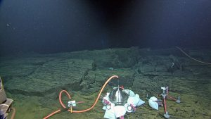 "The broadband seismometer (left) and low frequency hydrophone (right) are installed on the floor of Axial Seamount at the Central Caldera Site. The 7-function manipulator of ROPOS is connecting the extension cable to the medium powered junction box. The white bags inssulate the broadband from acoustic ""noise"" associated with curents flowing over the instrument."