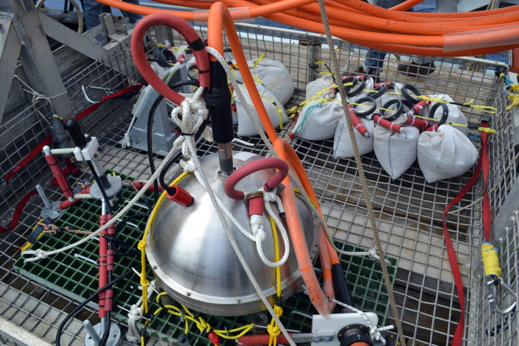 A low-frequency hydrophone (black tubular-shaped instrument in tripod with red legs), connected to a broadband seismometer, awaits installation by the Remotely Operated Vehicle ROPOS that will install this sensor in the International District 2 Site. Sand/gravel bags in the background will be piled over the broadband to dampen any noise by local currents. Photo credit: Mitch Elend, University of Washington, V14.