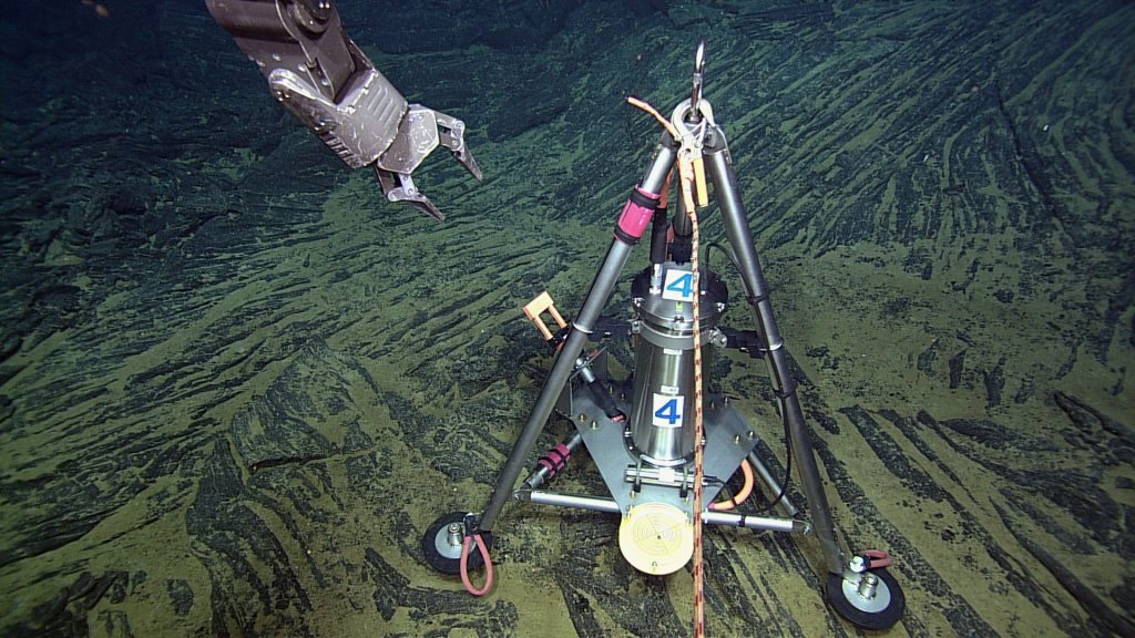 A bottom pressure-tilt instrument is installed at the summit of Axial Seamount in the International District hydrothermal field. This instrument measures the rise and fall of the seafloor due to melt migration in the subsurface. Currently, the seafloor is rising and this is believed to reflect the influx of magma into the core of the volcano.The instrument rests on a frozen lava flow - called a sheet flow. The small black marble in the yellow plate at the instrument base indicates that the platform it level. Photo credit: NSF-OOI/UW/CSSF; Dive R1723; V14.