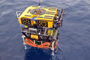 The ROV ROPOS has an RSN-OOI , medium-powered junction box, MJ03C, secured to its underbelly for transport to the International District hydrothermal vent field. The junction box will provide power and communication to a diverse suite of chemical, temperature, and biological sensors, in addition to a digital still camera. Photo credit: NSF-OOI/UW/CSSF; Dive R1717; V14.