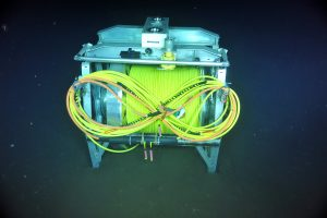 The ROCLS cable drum is unlatched on the seafloor at the base of Axial Seamount near PN3A at a depth of 2600 m. The cable, once plugged into a junction box and Primary Node, will power and communicate with ~2600 m-tall (8500 ft) instrumented moorings, as well as seafloor instruments. Photo Credit: NSF-OOI/UW/CSSF; Dive R1715; V14.