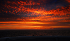 Viewed from the bow of the R/V Thompson, the sun setting behind the Olympic Mountains was a serene scene, and a great way to kick off the VISIONS '14 3-month Expedition.  Photo credit: Landung (Don) Setiawan, University of Washington, V14