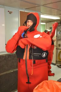 """University of Washington, School of Oceanography undergraduate, Jesse Turner, practises getting into a """"gumby"""" suit during a safety meeting onboard the R/ V Thomas G. Thompson. Photo Credit: Mitch Elend, University of Washington, V14."""