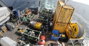 Panoramic view of the R/V Thompson fantail as it departs for Axial Seamount on the VISIONS'14 OOI expedition. Green-sided frames are junction boxes that will be installed at the volcano and they willl host myriad instruments. The central drum holds yellow extension cable that will connect one of the juction boxes to Primary Node 3B, providing power and bandwith to this subsea observatory.  Photo credit: Skip Denny, University of Washington, V14