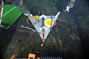 This short-period seismometer was deployed on a flat sheet flow ~ 1.3 km east of the ASHES hydrothermal field in 2013. The black ball in the yellow circle shows that it is perfectly level, helping to insure that the highest quality data comes off of this network. Axial Volcano is likely to be quite seismically active and we are anxious to get the real-time data on shore next year. This will help us understand magma and fluid migration in the subsurface of the volcano...and eventually these data may help us predict an eruption. VISIONS '13, Leg 4. Several earhquakes were detected in real-time during testing of these seismometers in 2013. Photo credit: NSF-OOI/UW/CSSF.