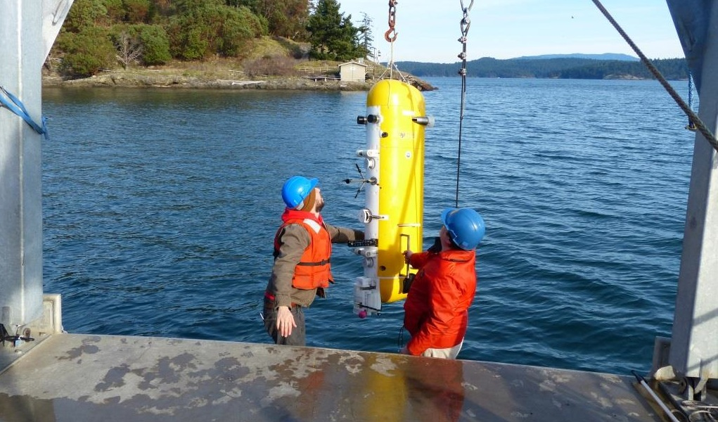 The Deep Profiler vehicle being installed on the mooring cable at the Friday Harbor test site. The FHL Pump House, which contains the power supply and other shore equipment, is shown in the background.
