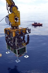 During the UW-OOI-NSF VISIONS'13 Expedition, the remotely operated vehicle ROPOS installed three medium power J-Boxes (secondary nodes) utilizing their special 4,000 lb heavy lift capabilities. ROPOS took this RSN J-Box down on dive R1601. The broad feet on the J-Box are used for installation in heavily sedimented areas. This was an unusually calm day at sea in the NE Pacific.  Photo Credit: Mitch Elend, University of Washington.