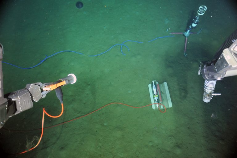 During ROPOS Dive 1629 of the VISIONS'13 Expedition, a current meter (tripod with red legs) and pressure sensor (SBE) were powered up and tested using through the medium powered J-box MJ01A. The ROV ROPOS provided power and communications and the data were streamed live up to the R/V Thompson through ROPOS's fiber optic tether. Here , the water depth was 10,000 ft.