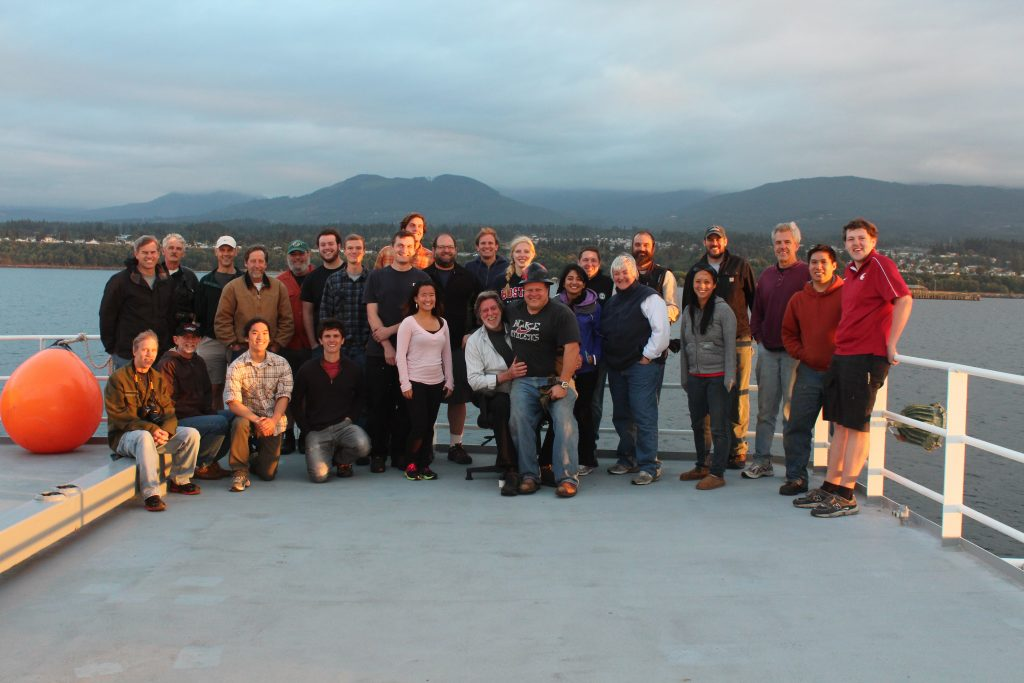 The team photo for Leg 4 on one of the forward decks of the R/V Thompson. The hills outside of Victoria BC are in the background.