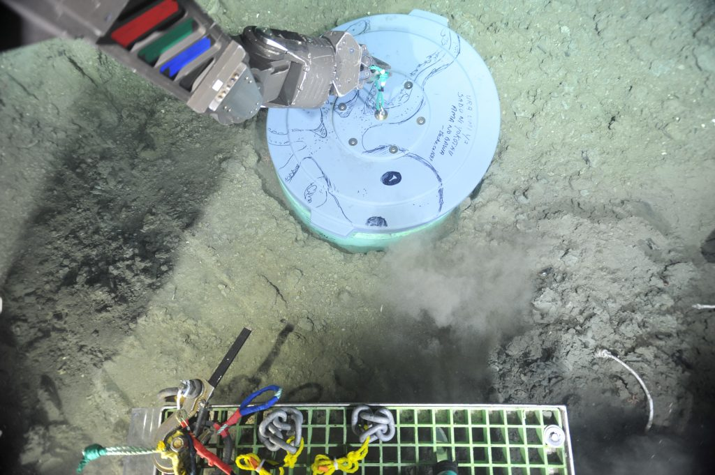 This caisson is buried to about 1 m depth beneath the sediments. Next year a broadband seismometer will be placed in it and connected to the cable, providing real-time detection and location of earthquakes. A cover was placed over the caisson to keep sediment from falling into it and animals out. Photo credit: NSF-OOI/UW/CSSF.