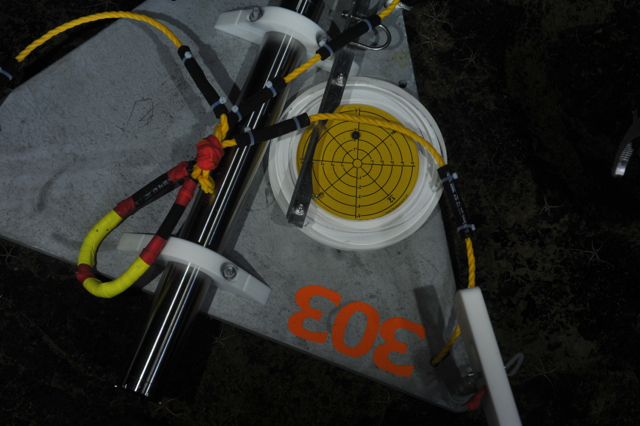 Part of the work required to properly install a seismometer on the seafloor is to ensure that the instrument is level. The yellow disk, shown here, is placed on the seismometer by ROPOS. The legs of the seismometer platform are then adjusted until a level reading is achieved. VISIONS '13 Dive 1617  	Credit: NSF-OOI/UW/CSSF