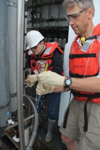 Julie Nelson and Orest Kawka sample the CTD water cast after collecting samples from the base of Axial Seamount. Photo by Allison Fundis