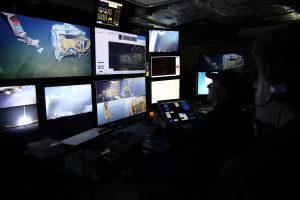 Chief Scientist John Delaney (right) narrates the live video stream as ROPOS pilot Josh Chernov approaches ROCLS, the remotely operated cable laying system, on the seafloor. Photo by Allison Fundis