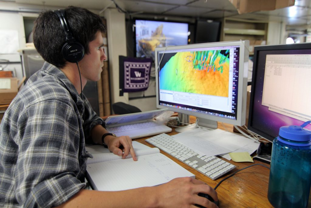 Undergraduate student Brendan Philip looks at data collected with the ship's multibeam sonar to image methane bubble plumes in the water column. (photo: Allison Fundis)